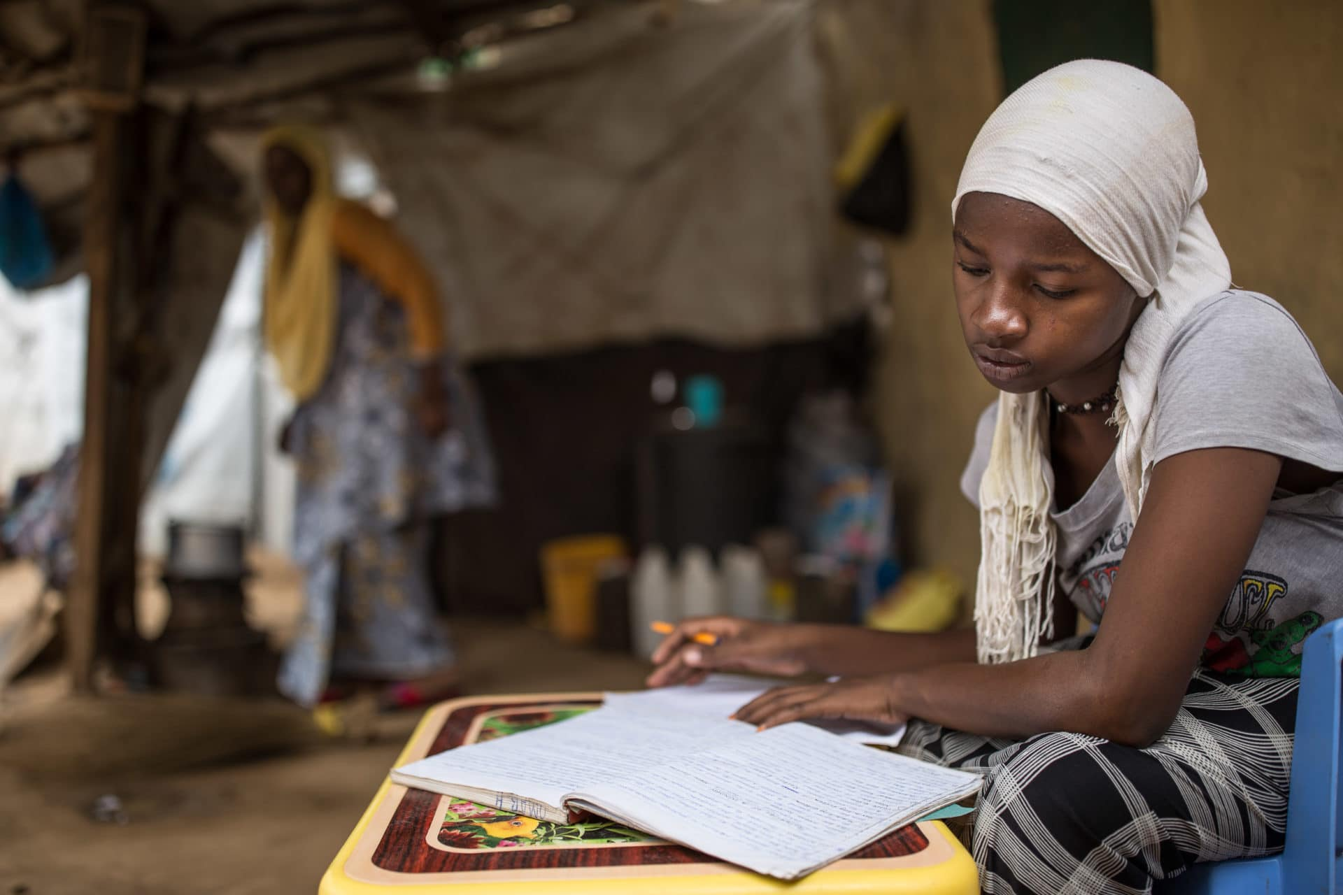 A young refugee studies at her home.